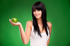 Beautiful brunette woman with green apple on green background Royalty Free Stock Photos
