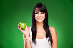 Beautiful brunette woman with green apple on green background Royalty Free Stock Photography