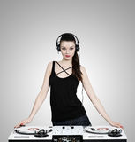 Beautiful brunette woman with headphones and turntables. Beautiful brunette woman with headphones and dj mixer and two white turntables royalty free stock photos