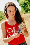 Beautiful woman with headphones on the road holding a passport with money. stock photo