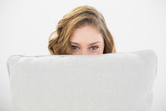 Beautiful brunette woman hiding her face behind a white pillow Stock Photography