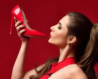 Beautiful brunette woman hold red shoe high hill on dark red. Background Stock Photo