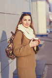 Beautiful brunette woman holding a bag and cup of hot tea or coffee, standing in the street Stock Image