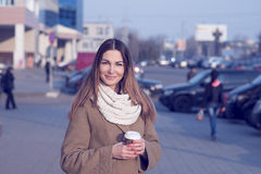 Beautiful brunette woman holding a bag and cup of hot tea or coffee, standing in the street Royalty Free Stock Photography