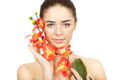 Beautiful brunette woman holding branch of orchid Stock Photos