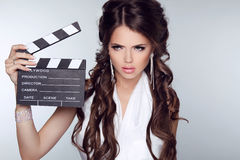 Beautiful brunette woman holding Clapper Board against a grey ba Royalty Free Stock Photography