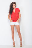 Beautiful brunette woman holding her hands in pockets. Royalty Free Stock Photos