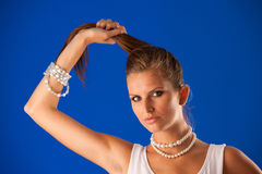 Beautiful brunette woman holding ponytail in her hand over vivid Royalty Free Stock Photography