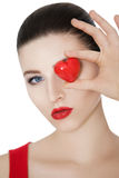 Beautiful brunette woman holding red heart in front of the face. Stock Image