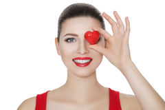 Beautiful brunette woman holding red heart in front of the face. Royalty Free Stock Image