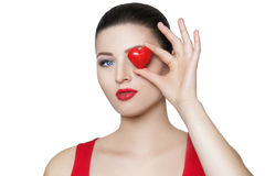 Beautiful brunette woman holding red heart in front of the face. Royalty Free Stock Photography