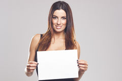 Beautiful brunette woman holding white blank sign Royalty Free Stock Image