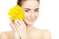 Beautiful brunette woman holding yellow flower Stock Photo