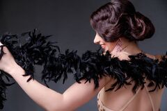 Free Beautiful Brunette  Woman In Boa From Ostrich Feathers Sits In Front Of The Camera With His Back And Posing Stock Images - 175169314