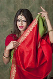 Beautiful brunette woman in indian red dress Stock Images