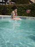 Beautiful brunette woman jumping in pool Royalty Free Stock Photography