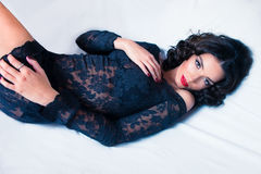 Beautiful brunette woman in lace black skirt laying down on whit. Beautiful young brunette woman in lace black skirt laying down on white sheets Royalty Free Stock Photo