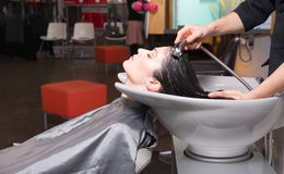Beautiful Brunette Woman Laid Back Wash Station Shampoo Pro. A day at the salon starts with shampoo Royalty Free Stock Photos