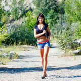 Beautiful brunette woman with a laptop walking on a mountain roa Stock Images