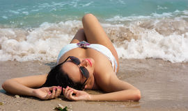 Beautiful brunette woman lies on the beach in waves. Beautiful brunette woman in glasses lies on the beach in waves stock images