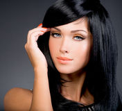Beautiful brunette woman with long black straight hair. Posing at studio Royalty Free Stock Photography