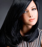 Beautiful brunette woman with long black straight hair. Posing at studio Royalty Free Stock Images