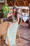Beautiful brunette woman in long dress and hat relaxing in beach restaraunt. Brunette woman in long dress and hat relaxing in beach bar stock photos