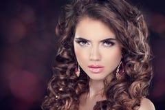 Beautiful brunette woman. Long wavy hair. Fashion earring. Profe Royalty Free Stock Photo