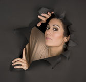 Beautiful Brunette Woman Looks Sideways Through Torn Hole Royalty Free Stock Photo