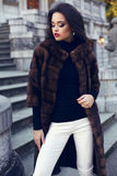Beautiful brunette woman in luxurious fur coat posing on stairs Stock Photos