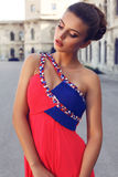 Beautiful brunette woman in luxurious red dress and evening makeup