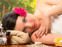 Beautiful brunette woman lying down in outdoor spa Royalty Free Stock Photo