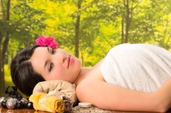Beautiful brunette woman lying down in outdoor spa Stock Photo