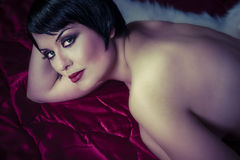 Beautiful brunette woman lying naked. On red silk Stock Image