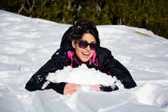 Beautiful brunette woman  lying on the snow ,enjoying the winter snow Royalty Free Stock Photography
