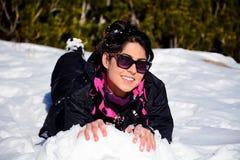 Beautiful brunette woman  lying on the snow ,enjoying the winter snow Stock Image
