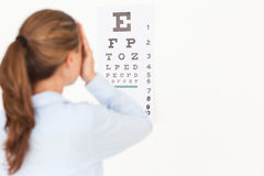Beautiful brunette woman making an eye test Royalty Free Stock Photo