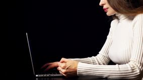 Beautiful brunette woman making online payment with her credit card using laptop. Black background, warm colors, space stock footage
