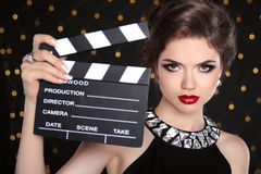 Beautiful brunette woman model holding film clap board cinema Royalty Free Stock Image