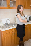 Beautiful brunette in woman in a modern kitchen. Stock Images