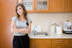 Beautiful brunette in woman in a modern kitchen. Royalty Free Stock Photography