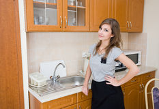 Beautiful brunette in woman in a modern kitchen. Royalty Free Stock Images