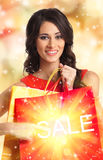 Beautiful brunette woman opening a red present bag Stock Image