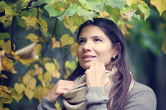 Beautiful brunette woman outdoors. Beautiful brunette woman portrait on autumn tree background Stock Photography