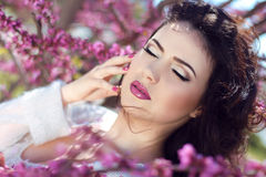 Beautiful brunette woman over pink brunch of tree, outdoors port Royalty Free Stock Photos