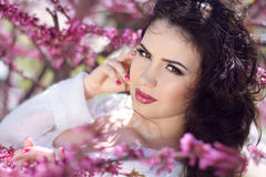 Beautiful brunette woman over pink brunch of tree, outdoors port. Rait, lifestyle Royalty Free Stock Photo