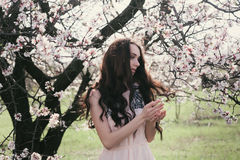 Beautiful brunette woman in the park standing near the blossom tree Royalty Free Stock Image