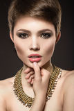 Beautiful brunette woman with perfect skin, bright makeup and gold jewelry. Beauty face. Picture taken in the studio on a grey background Royalty Free Stock Images
