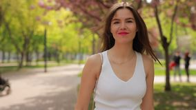 Pretty brunette woman with pink lips walking in a park stock footage