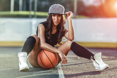 Beautiful brunette woman playing basketball on court outdoor. Sunset. Fitness girl with basketball ball playing game outdoor Royalty Free Stock Image